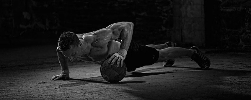 A man is doing push-ups with a ball